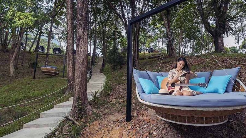 a lady on an outdoor sofa swing at the culvert kuching