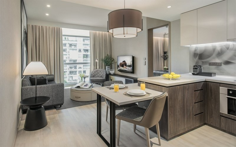 living room and kitchen of a suite in ascott orchard singapore