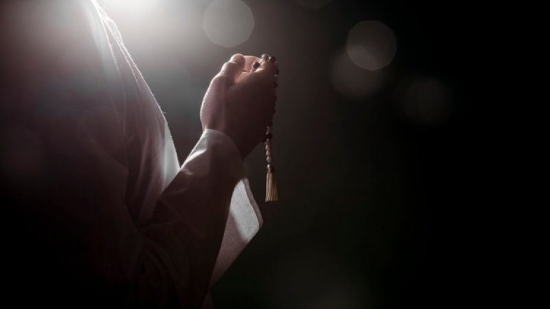 person holding prayer beads islam