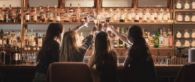 women clinking glasses at a bar