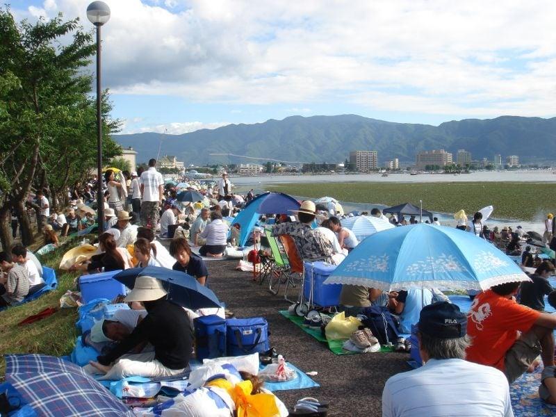 spectators on mats sitting along lake suwa