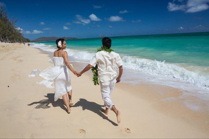 Newlyweds run along Waimanalo Beach, Waimanalo, Oahu, Hawaii