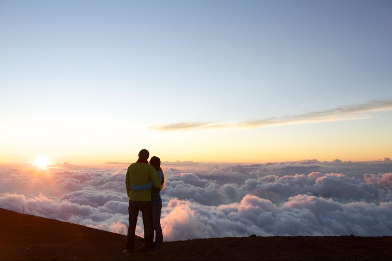 Couple watch rising sun, Haleakala, Maui