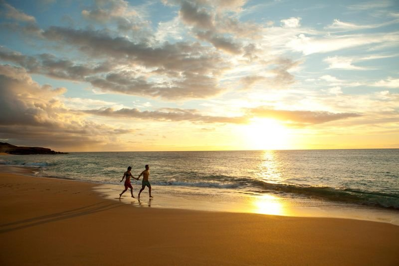 Couple run along Papohaku Beach, Papohaku, Molokai
