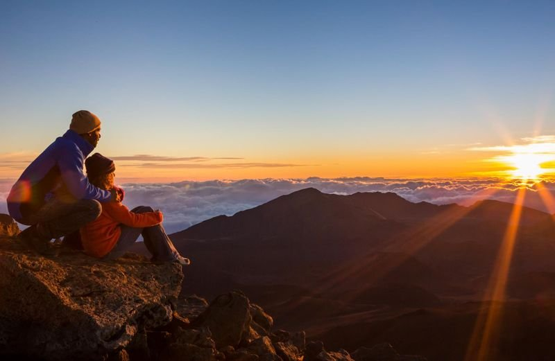 Couple watch the sun rise atop Haleakala, Haleakala, Maui